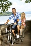 Happy couple riding on bicycle outdoor Stock Image
