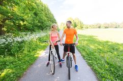 Happy couple riding bicycle outdoors Royalty Free Stock Images