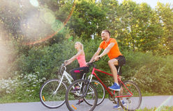 Happy couple riding bicycle outdoors. Fitness, sport, people and healthy lifestyle concept - happy couple riding bicycle outdoors at summer stock images
