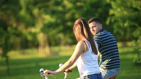 Happy couple riding a bicycle in the park. summer time. sunset. Happy couple riding a bicycle in the park stock footage