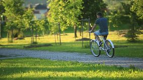 Happy couple riding a bicycle in the park. summer time. sunset. Happy couple riding a bicycle in the park stock video