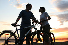 Happy couple riding bicycles outside, healthy life. Style fun concept. silhouette at sunset panoramic Royalty Free Stock Photo