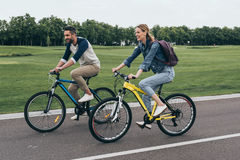 Happy couple riding bicycles together in park Stock Photo