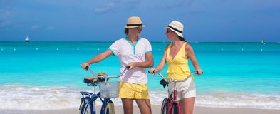 Happy couple riding bikes during tropical vacation Stock Images