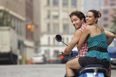 Happy Couple Riding On Moped In Street. Rear view portrait of a happy couple riding on moped in street Royalty Free Stock Photos