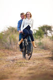 Happy couple riding old bicylce on dirt road Stock Image