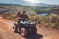 Happy couple riding on a quad bike Stock Photo