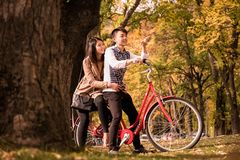 Happy couple riding on retro bicycle against the autumn background trees. The men runs a bicycle, a girl sits behind. Romantic image of two people on vacation stock photos