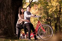Happy couple riding on retro bicycle against the autumn background trees. The men runs a bicycle, a girl sits behind. Romantic image of two people on vacation stock image