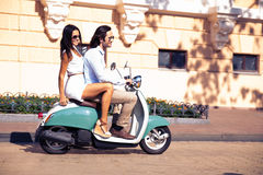 Happy couple riding a scooter Stock Photos