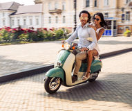 Happy couple riding on a scooter Royalty Free Stock Images