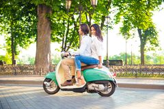 Happy couple riding on a scooter Stock Images