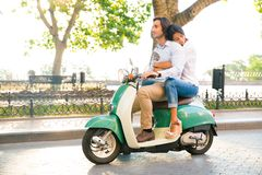 Happy couple riding on a scooter Stock Photo
