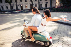 Happy couple riding a scooter Royalty Free Stock Image