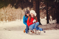 Happy couple riding a sled Stock Photos