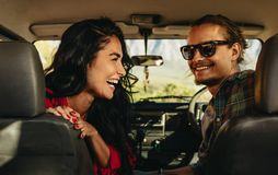 Happy couple on road trip. Rear view of a young couple on road trip. Smiling men and women looking back sitting in a car stock photo