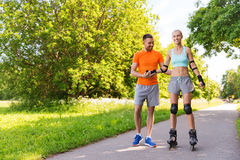 Happy couple with roller skates riding outdoors Royalty Free Stock Image