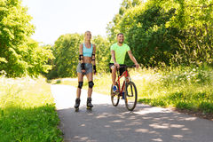 Happy couple with rollerblades and bicycle riding Royalty Free Stock Photos