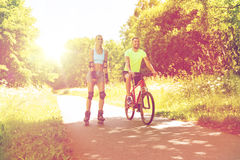 Happy couple with rollerblades and bicycle riding Royalty Free Stock Image