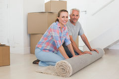 Happy couple rolling out new rug Royalty Free Stock Photo