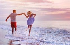Happy couple at romantic sea sunset. Happy couple runs in wave splashes at romantic sea sunset Stock Photo
