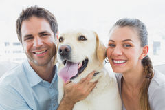 Happy couple rubbing their yellow labrador on the couch Stock Photo