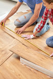 Happy couple with ruler measuring parquet board Stock Image