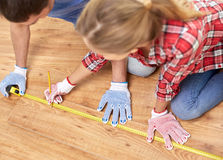 Happy couple with ruler measuring parquet board Stock Photos