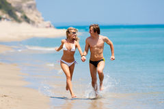 Happy couple running on beach Stock Photos