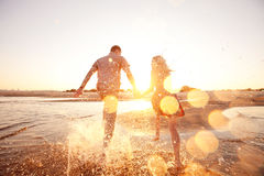 Couple running on the beach. Happy couple running on the beach royalty free stock photo