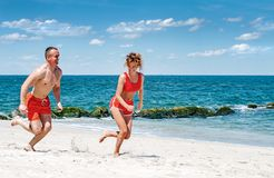 Happy couple running on beach. Man and woman jogging on the sea shore. stock photography