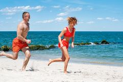 Happy couple running on beach. Man and woman jogging on the sea shore. royalty free stock image