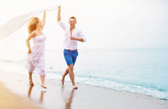 Happy couple running on the beach stock photography