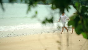 Happy couple running on the beach. Travel together. stock video footage
