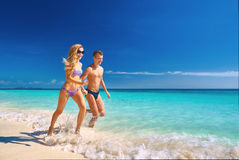Happy couple running on the beach Royalty Free Stock Image