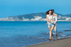 Happy couple running on the beach Stock Images