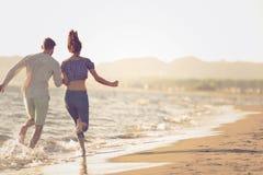 Happy couple running on the beach Stock Image