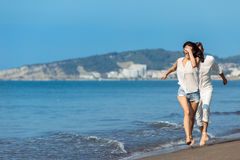 Happy couple running on the beach Royalty Free Stock Photo