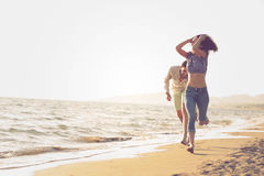 Happy couple running on the beach Royalty Free Stock Photos