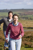 Happy couple running through countryside.  stock image