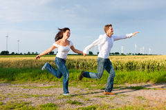 Happy couple running on a dirt road in summer Stock Photos