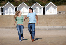 Happy couple running down beach Royalty Free Stock Photos
