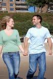 Happy couple running down beach stock image
