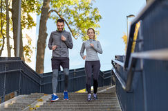 Happy couple running downstairs in city Royalty Free Stock Images