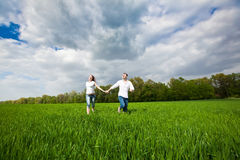 Happy Couple running on a grass. Happy young couple running in a green field Stock Photography