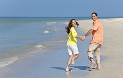 Happy Couple Running Holding Hands on A Beach Royalty Free Stock Images