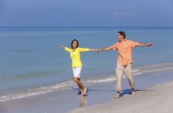 Happy Couple Running Holding Hands on A Beach Royalty Free Stock Image