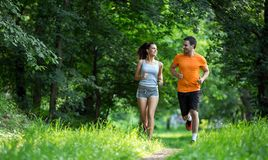 Happy couple running and jogging together. In nature stock images