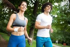 Happy couple running and jogging together outdoor. Happy couple running and jogging together in nature stock images