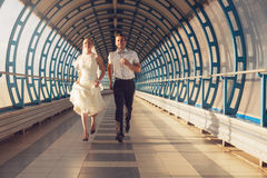 Happy couple running in long tunnel Royalty Free Stock Photo